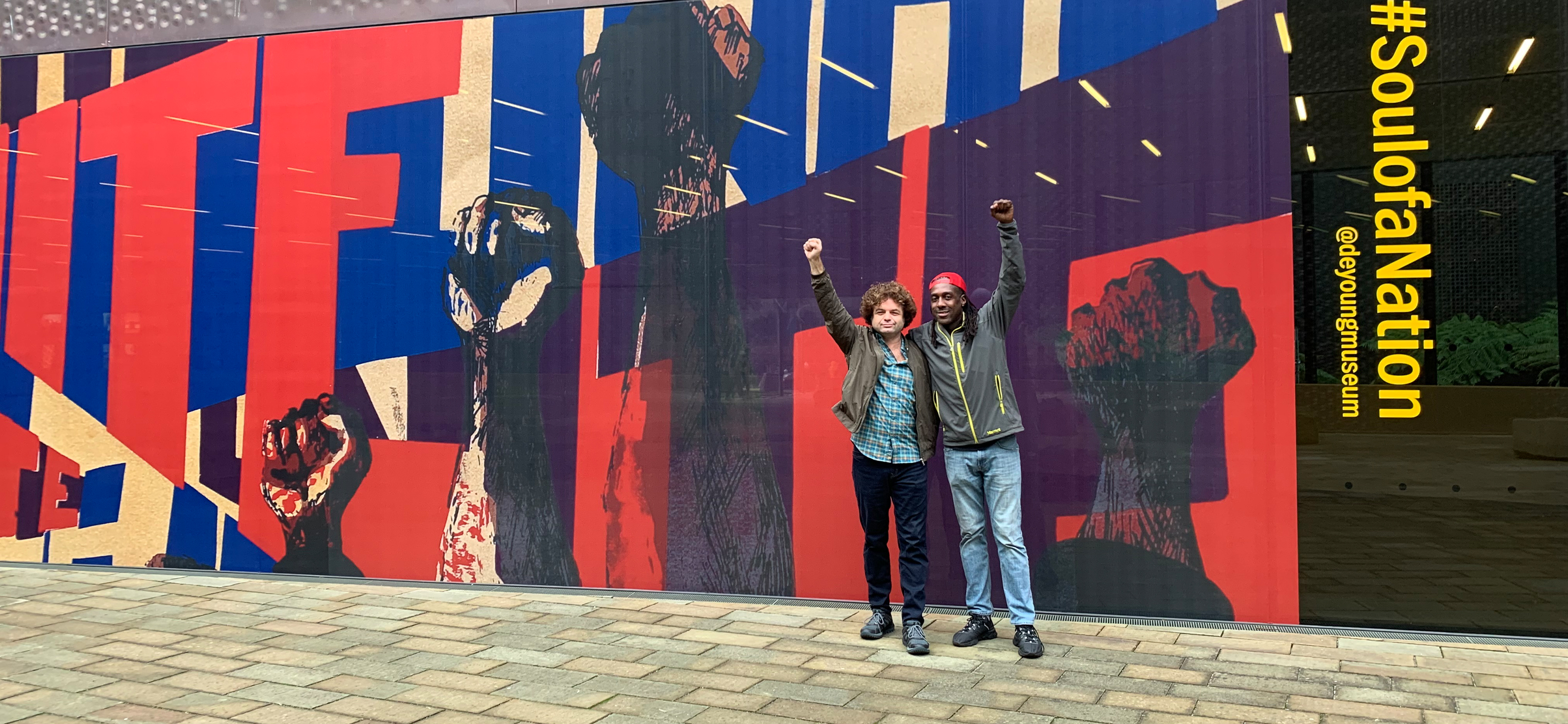 Two men stand together with one arm around each other and the other arm raised, in front of the red and blue graphic promoting the exhibition.